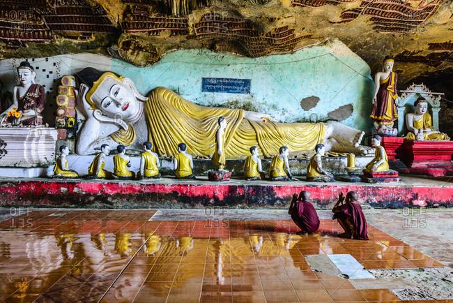 Phaan, Kayin, Myanmar - December 24, 2013: Asian monks praying to Buddha statue in temple
