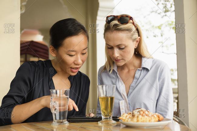 Businesswomen using digital tablet in cafe