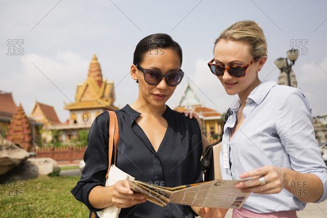 Tourists reading map near temple, Phnom Penh, Cambodia