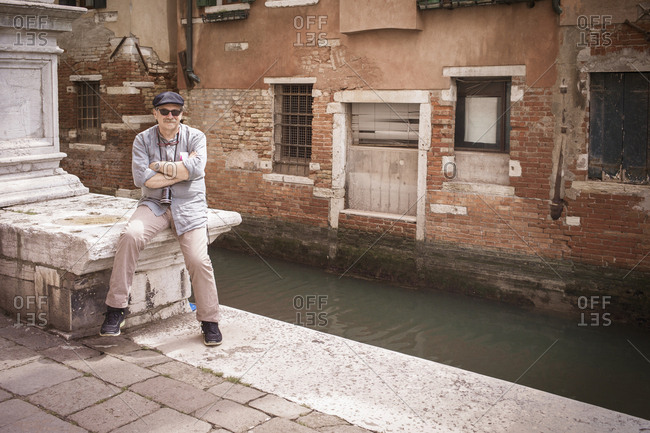 Caucasian tourist standing on canal waterfront, Venice, Veneto, Italy