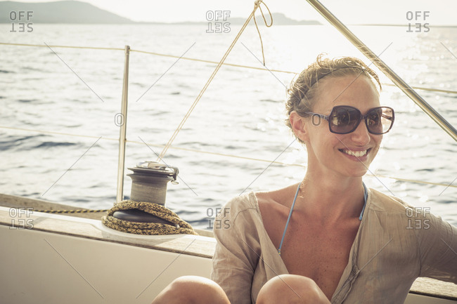 Smiling Caucasian woman sitting on boat deck