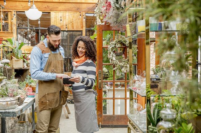 Employees using digital tablet in plant nursery