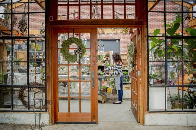 Mixed race employee working beyond doorway in plant nursery