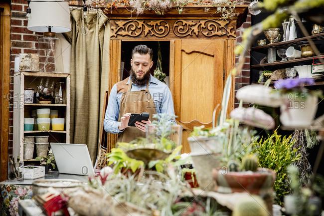 Caucasian employee using digital tablet in plant nursery