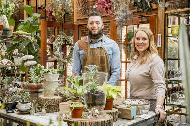 Caucasian employees smiling in plant nursery