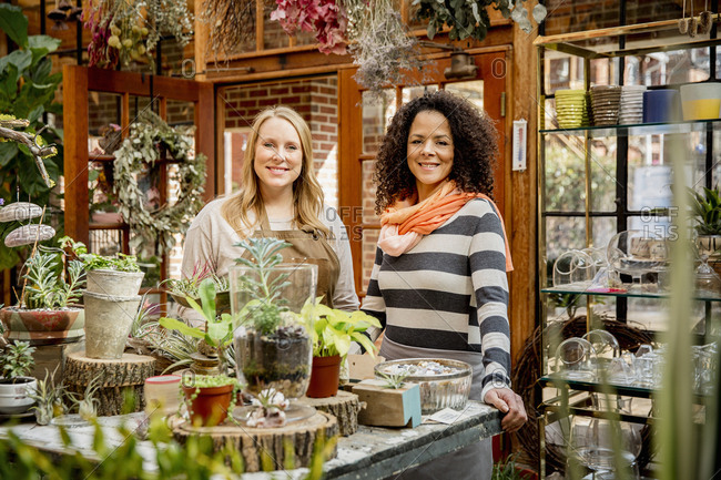 Employee and customer smiling in plant nursery