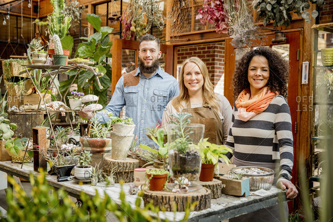 Employee and customers smiling in plant nursery