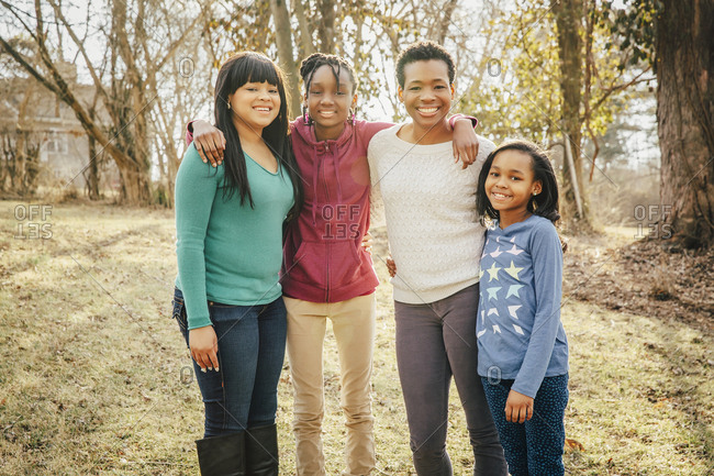 Black mother and daughters smiling outdoors