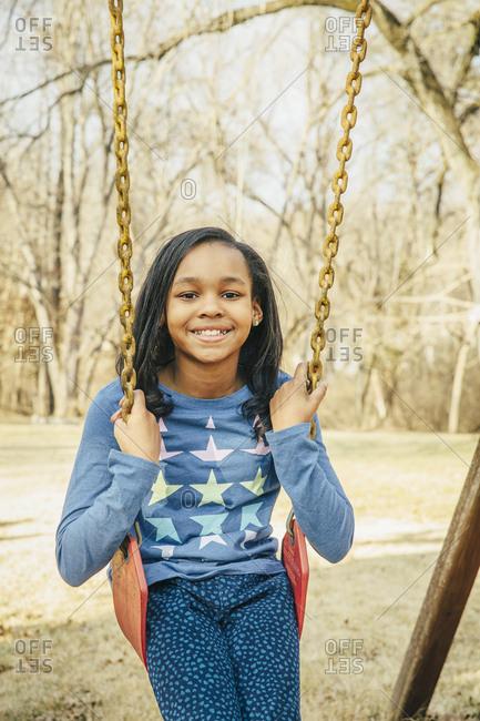 Black girl sitting on swing