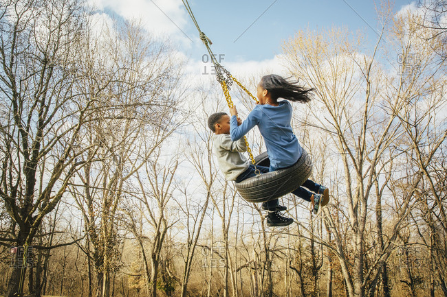 Black brother and sister playing on tire swing
