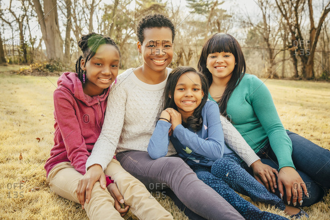 Black mother and daughters sitting outdoors