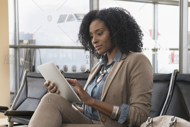 Businesswomen using digital tablet in airport waiting area