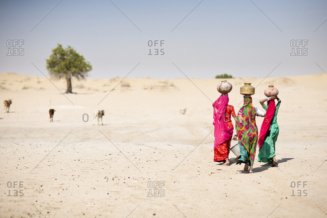 Women carrying water in traditional baskets in remote desert