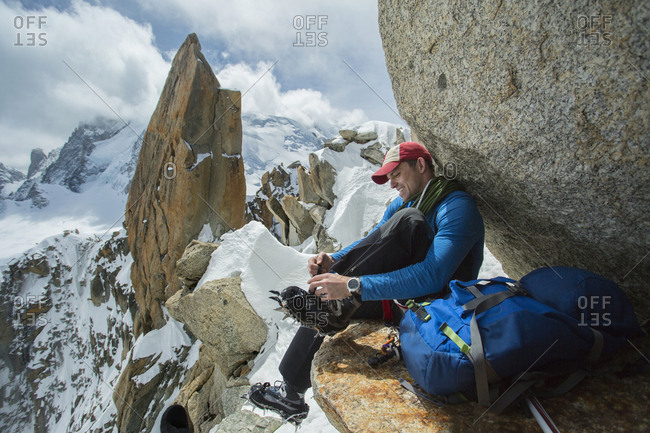 Caucasian hiker fastening ice cleats on rocky mountain, Chamonix, Haute-Savoie, France