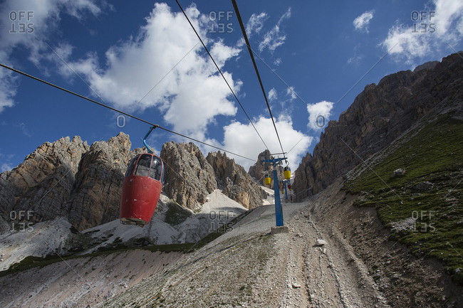 Low angle view of gondolas on line up remote mountainside