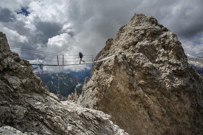 Caucasian hiker crossing rope bridge between rock formations