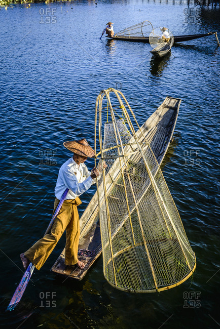 Asian fisherman fishing in canoe on river