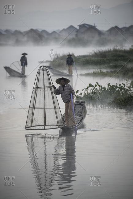 Asian fishermen fishing in canoes on river
