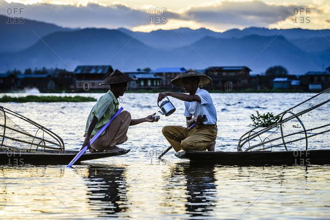 Asian fishermen sharing tea in canoes on river