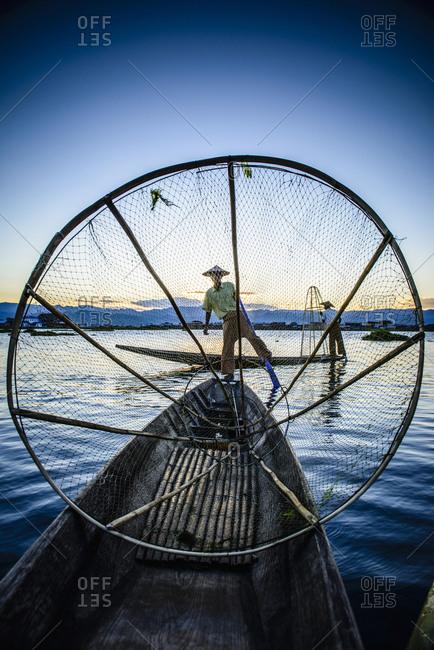 Asian fisherman using fishing net in canoe on river