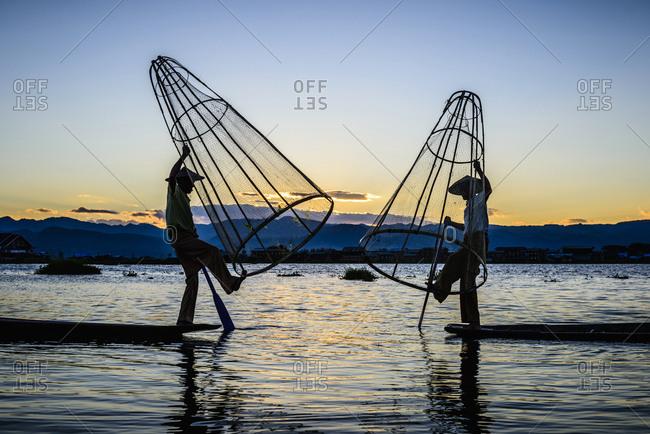 Asian fishermen using fishing nets in canoe on river