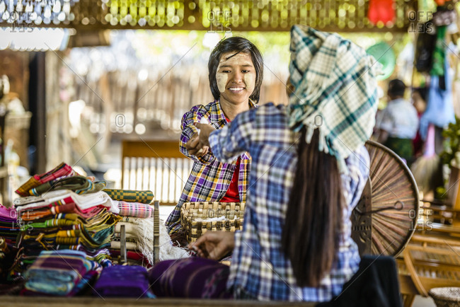 Asian teenage boy selling fabric at market