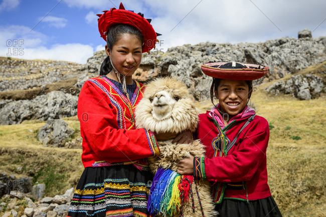 Hispanic sisters smiling with llama in rural landscape