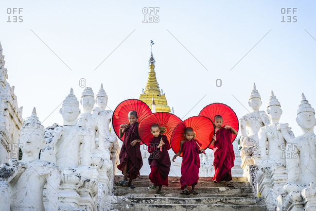 Asian children with parasols balancing on Buddhist shrine