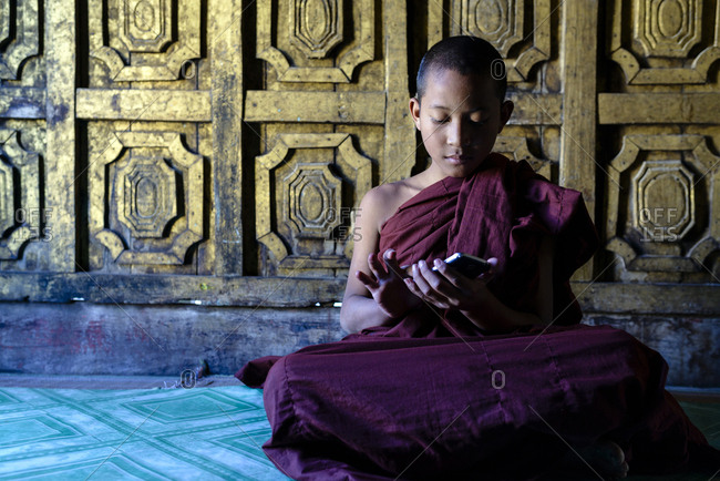 Asian monk-in-training using cell phone in temple