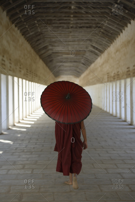 Asian monk-in-training carrying parasol in hallway