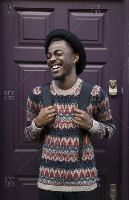 Laughing Black man wearing backpack near purple door