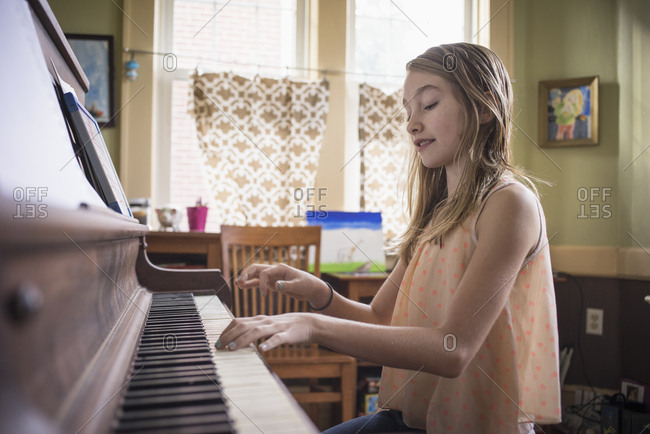 Caucasian girl playing piano in living room