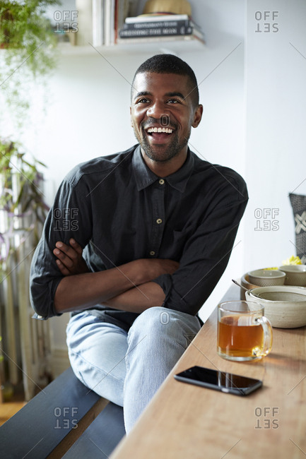 Black man with tea and cell phone at table