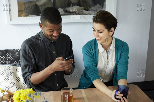 Couple using cell phone at table