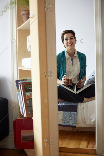 Woman drinking tea and reading in bedroom