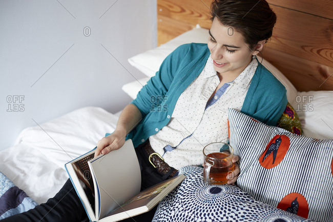 Woman drinking tea and reading in bed