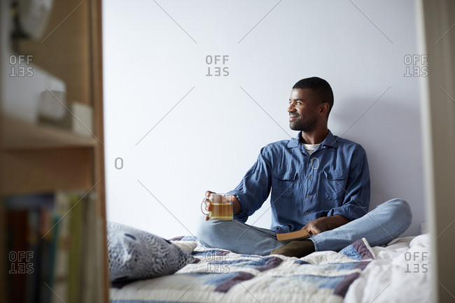 Black man drinking tea and reading on bed