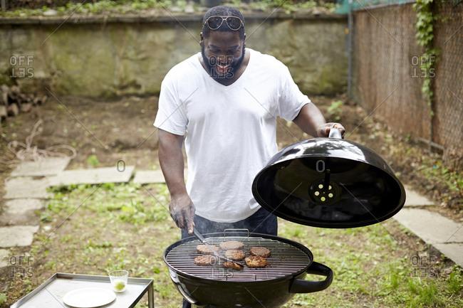 Black man grilling hamburgers at backyard barbecue