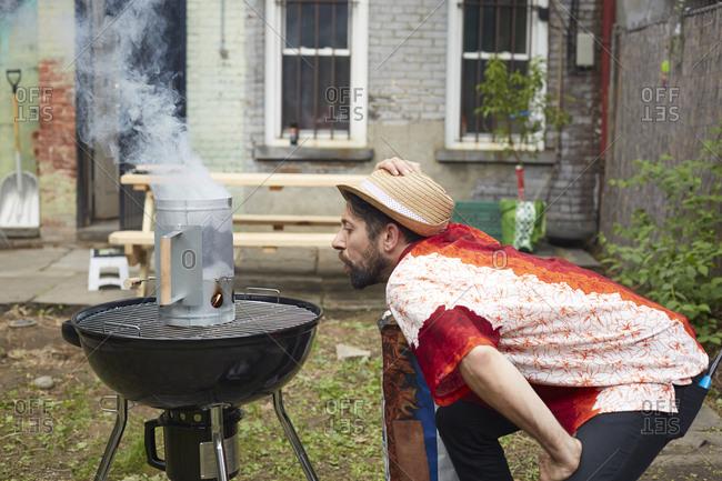 Caucasian man lighting charcoal for grill in backyard