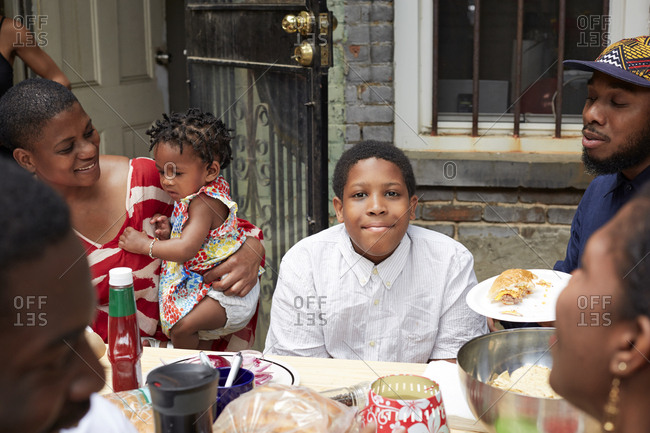 Family eating together at backyard barbecue