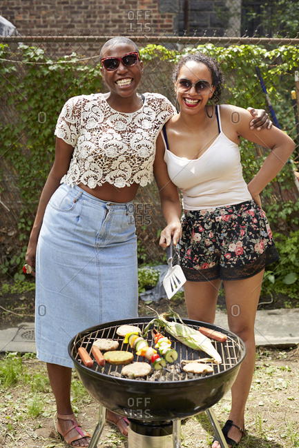 Women grilling vegetables at backyard barbecue