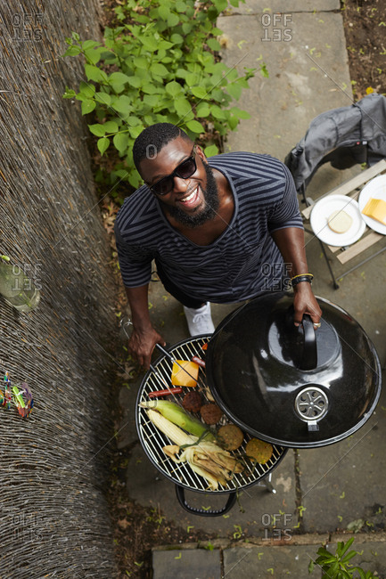 High angle view of African American man grilling at barbecue