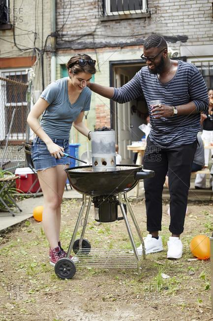 Couple lighting charcoal for backyard barbecue
