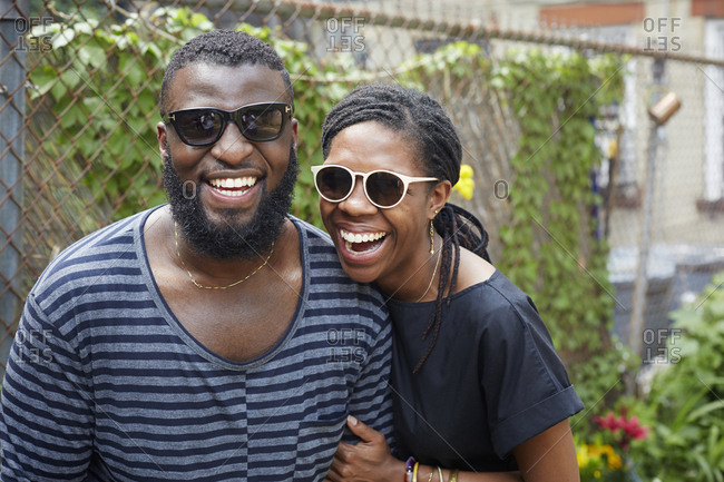 Smiling couple wearing sunglasses near fence