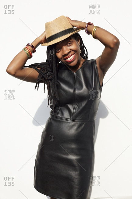 African American woman wearing leather dress and straw hat