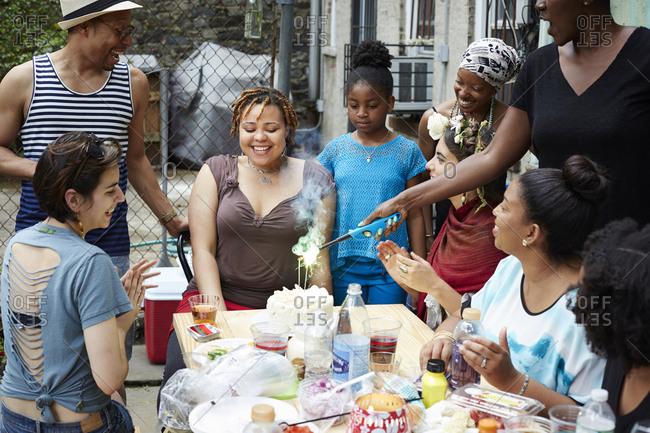 Friends celebrating birthday party in backyard