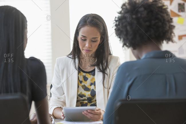 Businesswoman using digital tablet in office meeting