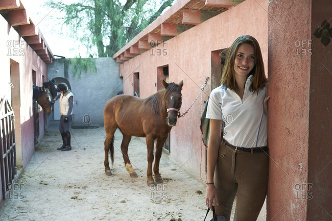 Woman smiling at horse stables on ranch