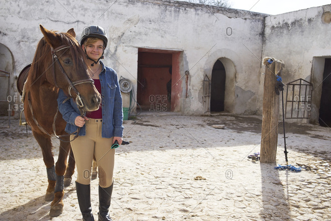 Caucasian teenage girl leading horse in stable on ranch