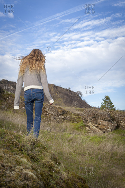 Girl walking on grassy hillside